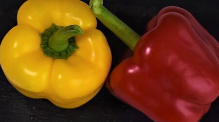 Two bright yellow and red peppers on a black board
