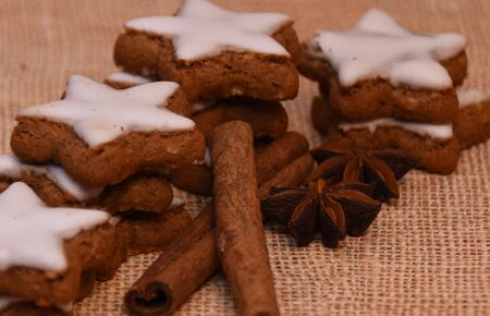 Baked cookies with cinnamon and white icing, anise stars on a canvas background