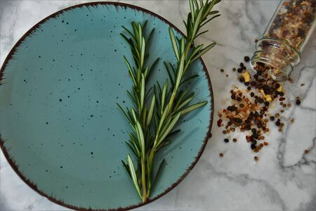 Sprigs of rosemary in a blue round plate on a white marble background Reklamní fotografie
