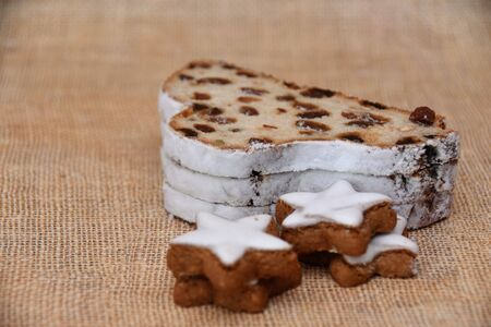 Christmas German traditional pastries, stars with cinnamon and stollen with raisins on a background of natural canvas