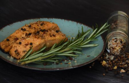 Two pieces of sturgeon fried fish with a sprig of rosemary in a glass jar on a black background Reklamní fotografie