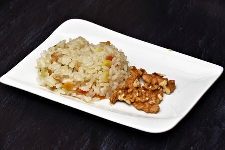 Boiled rice with vegetables and walnuts on a black plate