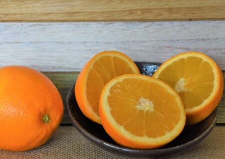 Halves and a whole orange and a glass mug with juice on the background of wooden boards