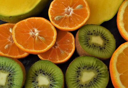 Halves of tropical fruits, clementines, orange, kiwi and mango Reklamní fotografie