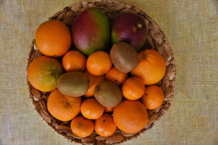 Mangoes, kiwi, oranges and tangerines in a wicker bowl
