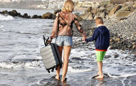Young slender woman walks with a cherman and a boy along the ocean