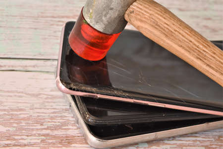 hammer and broken smartphone on a wooden table Stock fotó