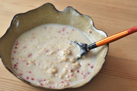 oatmeal porridge with milk and berries in a plate with a wooden spoon