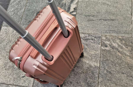 pink ladies' travel suitcase stands on the marble platform