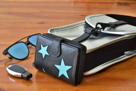 women bag mirrored glasses car keys and wallet on a wooden table