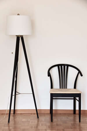 floor lamp and chair near white wall