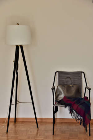 Floor lamp and chair with handbag and blanket against the wall