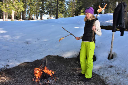 girl cooks sausage and bread on the fire