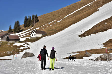 man and a woman are walking holding hands in the mountains