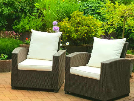 two armchairs with cushions stand in the courtyard near the flowers