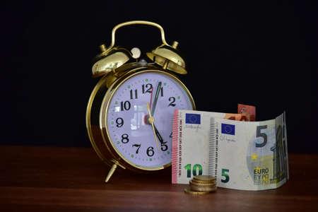 money and alarm clock on black background