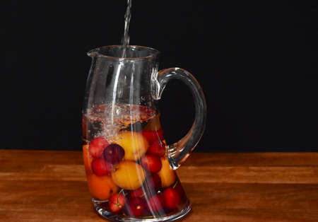 water is poured into a glass decanter with cherries and apricots