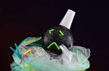 black earth globe and plastic trash in a bag