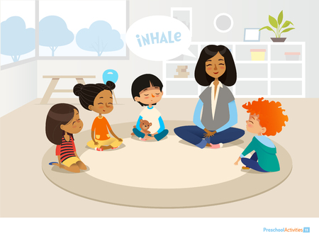Smiling kindergarten teacher and children sitting in circle and meditating.