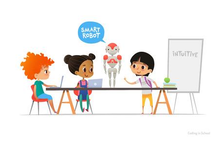 Sonriendo a niños sentados en ordenadores portátiles en torno a robot inteligente de pie en la mesa en el aula de la escuela.