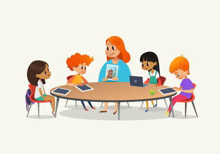 Redhead female teacher showing picture to children sitting around round table at class with laptop and tablet pc. Kids using gadgets during lesson at primary school. Colorful vector illustration