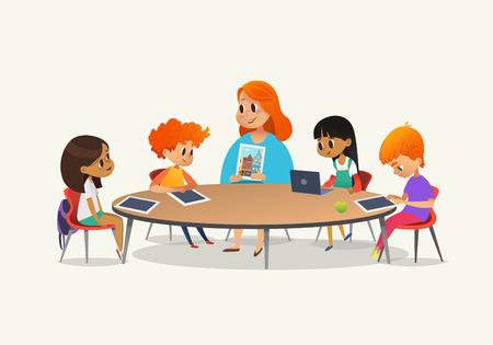 Redhead, professora mostrando imagem para crianças sentadas em torno de mesa redonda em aula com laptop e tablet pc. Crianças usando gadgets durante a aula na escola primária. Ilustração vetorial colorida