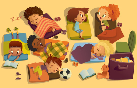Nap time in the kindergarten. Group of multiracial girls and boys have a nip time at a colorfill nap mats. Preschool dream time. Two girls gossip during daytime sleep Stock Photo