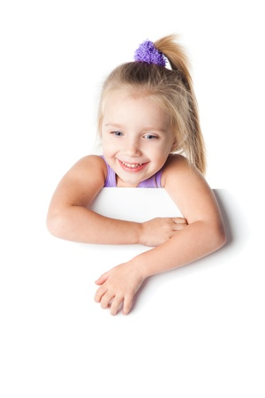 smiling little girl looking over empty board isolated Stock Photo - 17415175