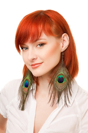 portrait of young beautiful redhead woman with peacock earrings