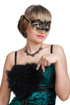 Beautiful girl in green evening dress with necklace and earrings  in carnival mask hodling fan  photo