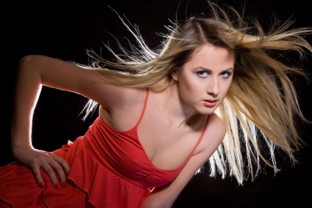 flying hair: portrait of blonde girl in red dress with flying hair