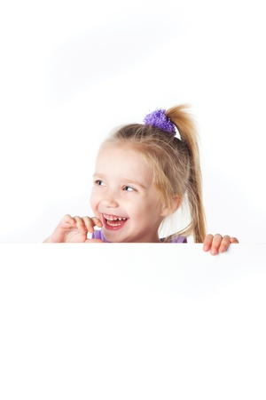 laughing little girl looking over empty board isolated Stock Photo - 17680684