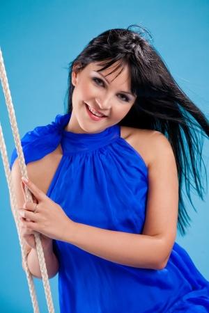 happy beautiful brunette girl in stduio over blue  Stock Photo