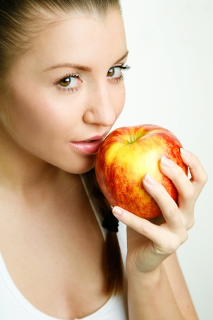 Beautiful young woman eating red apple Stock Photo - 17891440