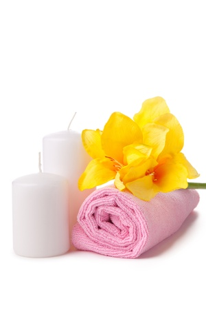 two candles, pink towel and yellow flower. spa composition over white background Stock Photo