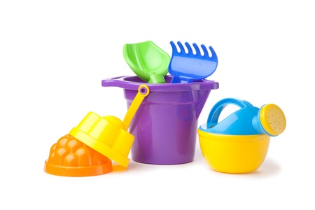 wateringcan: toy purple bucket with spade and rake, watering-can over white background Stock Photo