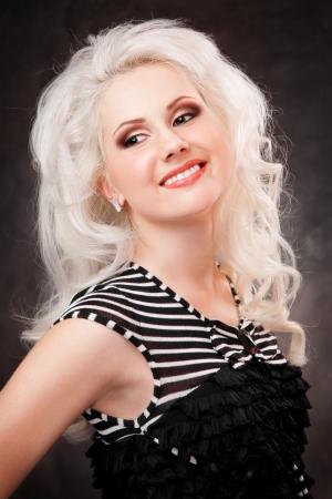 studio shot of a young, beautiful, blonde woman in black dress Stock Photo