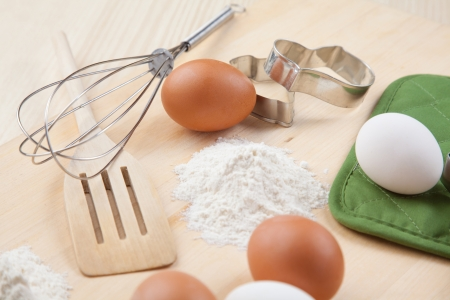 eggs, flour, cookie mold and whisk on wooden board together Stock Photo