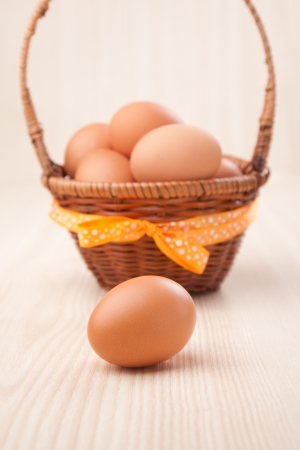 one egg in front of little basket with yellow bow on wooden table  photo