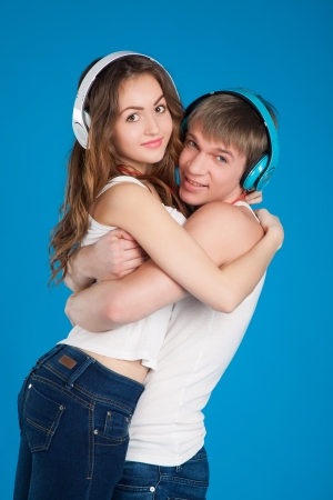 jeans girl: young love couple. Boy holding girl. wearing headphones, listening music in the studio over blue background