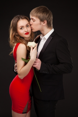 beautiful elegant love couple wearing suit and red dress with white rose in the studio over black background