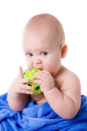 A beautiful  baby wrapped in a blue towel biting green ball Stock Photo - 18824338