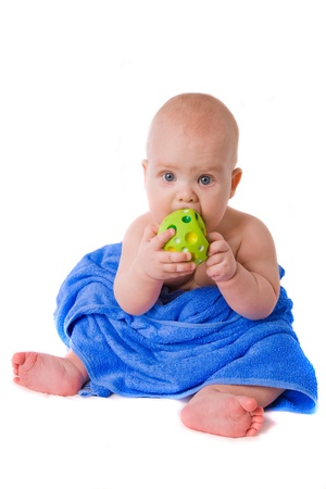 little child  in a blue towel biting green ball Stock Photo - 18824265