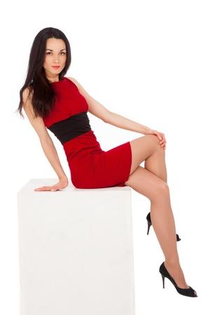 schöne dünne Brünette Frau im roten Kleid sitzt auf dem Würfel über weißem Hintergrund Standard-Bild