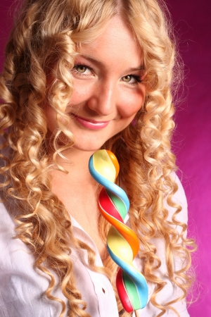beautiful blonde smiling  girl with curly hair holding big lollipop over pink background  photo