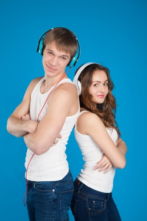 young love couple wearing headphones, listening music in the studio over blue background  photo