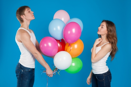 Young boy presenting baloons to a girl over blue background photo