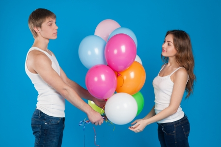 Young boy presenting baloons to a girl over blue background