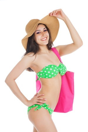 sexy young  brunette girl wearing green swimsuit and big hat, holding pink bag