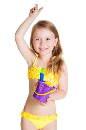 klein meisje op strand: kleine blonde gelukkig meisje in gele zwembroek bedrijf speelgoed paarse emmer over een witte achtergrond